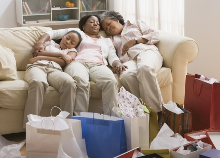 wearying: Three generations of African women resting on sofa