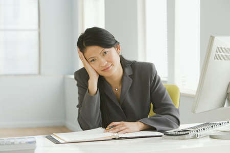 wearying: Asian businesswoman sitting at desk with head in hand