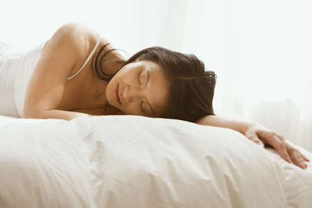 wearying: Asian woman sleeping in bed LANG_EVOIMAGES