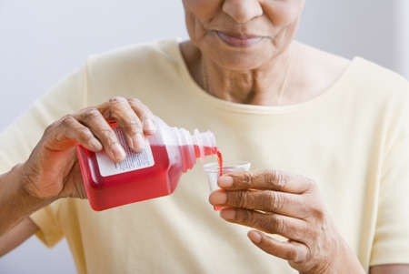 Close up of senior African woman pouring medication into cup Stock Photo