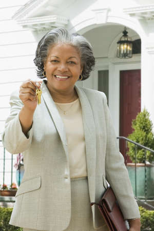 one mid adult woman only: African female real estate agent holding keys to house LANG_EVOIMAGES