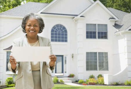 only seniors: African female real estate agent holding contract to house