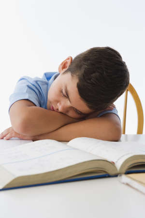 wearying: Hispanic boy napping on textbook LANG_EVOIMAGES