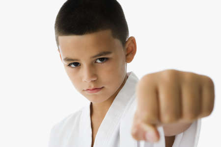 arts and entertainment: Studio shot of Hispanic boy in martial arts stance
