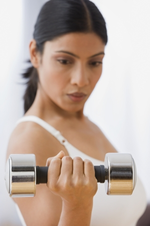 exerting: Indian woman lifting weights LANG_EVOIMAGES