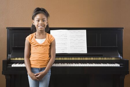 musicality: African girl standing in front on piano