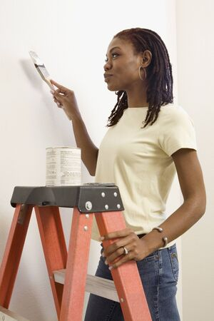 africanamerican: African woman on ladder painting