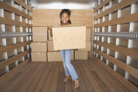 African girl holding box in moving truck Stock Photo - 16093319