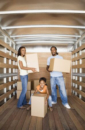 go inside: African family holding boxes in moving truck