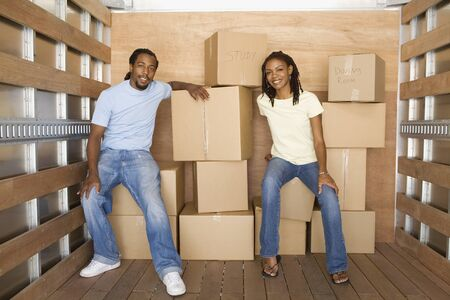 African couple in back of moving truck LANG_EVOIMAGES