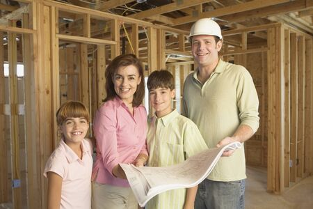 conferring: Family with blueprints on construction site LANG_EVOIMAGES