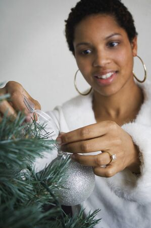 African woman putting ornament on Christmas tree