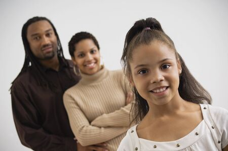 Studio shot of African girl smiling with parents in background Stock Photo - 16093352
