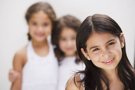 Hispanic girl smiling with sisters in background Stock Photo - 16093353