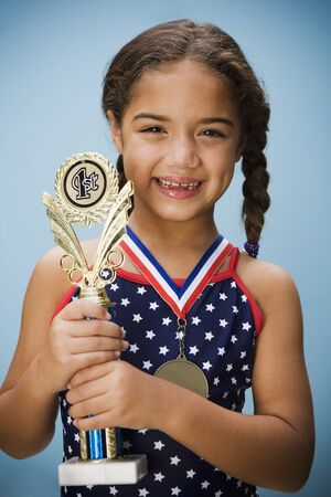 prevailing: Hispanic girl smiling with medal and trophy