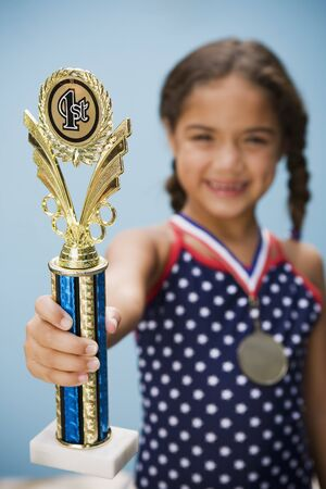 differential focus: Hispanic girl holding medal and trophy LANG_EVOIMAGES