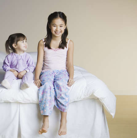 only two people: Portrait of Asian sisters sitting on bed