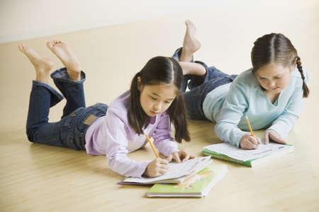 japanese ethnicity: Two girls doing homework on floor