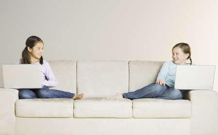sofa: Two girls holding laptops on sofa LANG_EVOIMAGES
