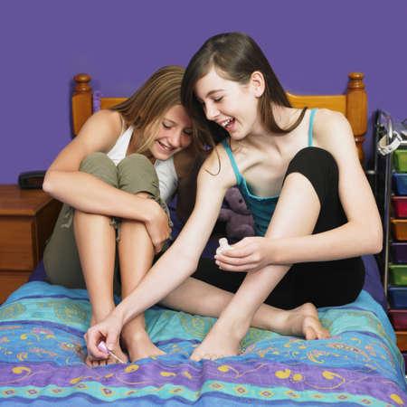 teenaged girl: Teenaged girl painting friend's toenails