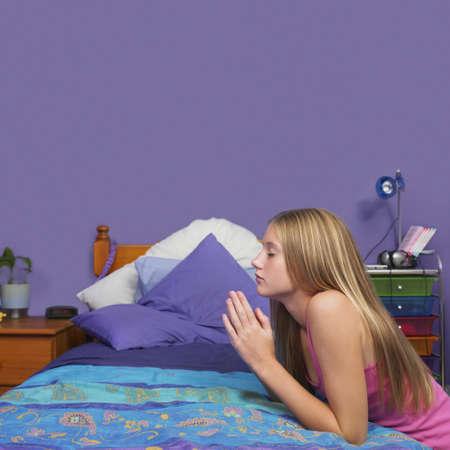 teenaged girl: Teenaged girl praying in bedroom