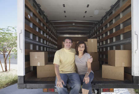 Portrait of couple sitting in moving truck LANG_EVOIMAGES