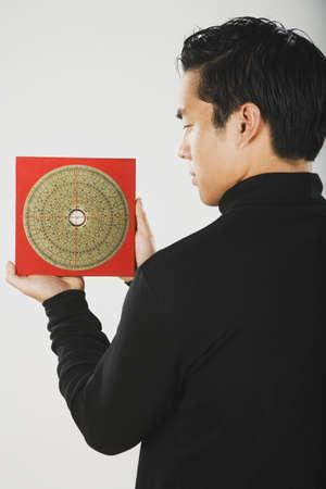 shui: Asian man holding feng shui chart