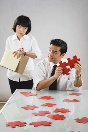 Asian woman timing man putting together puzzle Stock Photo