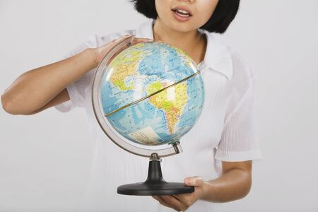 Asian woman looking at globe Stock Photo