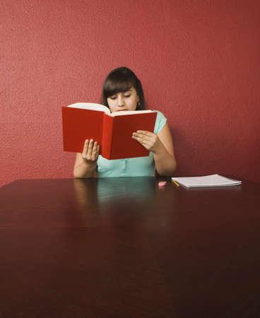 teenaged girl: Hispanic teenaged girl studying LANG_EVOIMAGES