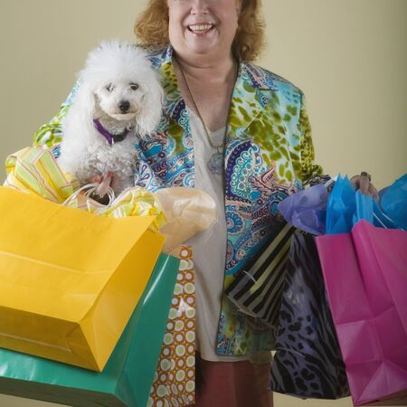 Senior woman holding shopping bags and dog