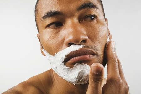 Asian man applying shaving cream