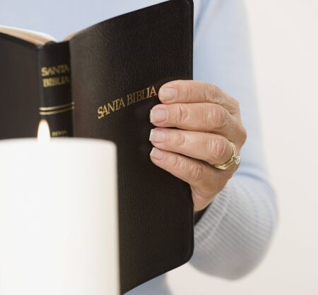 Close up of woman holding Spanish bible 스톡 콘텐츠