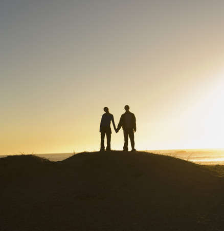 couple lit: Silhouette of couple holding hands on hill