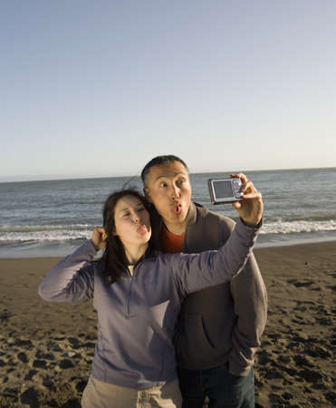 Asian couple taking own photograph at beach Stock Photo - 16093698
