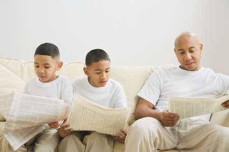imitating: Indian father and sons reading newspaper