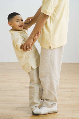 alike: Indian boy standing on father's feet
