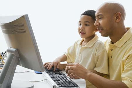 child studying: Indian father and son looking at computer