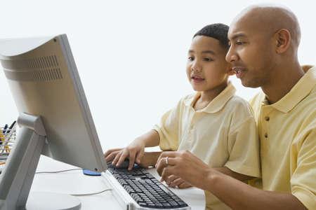 niños estudiando: Padre indio y el hijo mirando la computadora LANG_EVOIMAGES