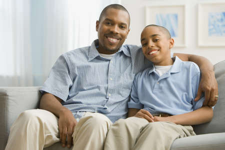 alike: Portrait of African father and son on sofa