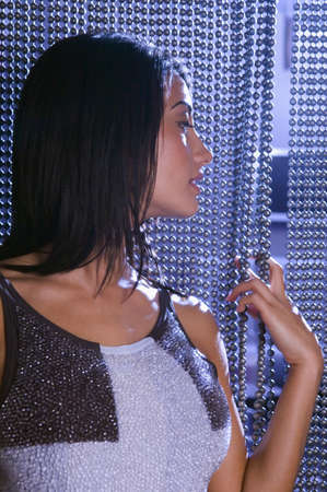 Hispanic woman looking through beaded curtain Stock Photo - 16094576