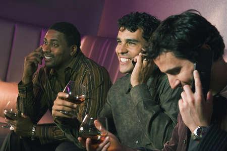 lounge: Multi-ethnic men talking on cell phones