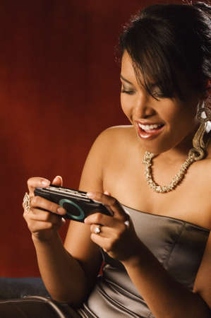 African woman playing hand held video game Stock Photo - 16094596