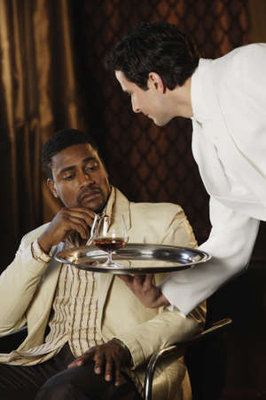 only mid adult men: Waiter bringing African man a drink LANG_EVOIMAGES