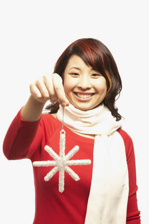 holding a christmas ornament: Portrait of Asian woman holding Christmas ornament LANG_EVOIMAGES
