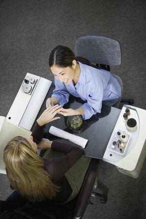 joining services: Asian nail technician filing client's fingernails