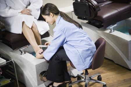 appendage: Asian nail technician filing client's toenails