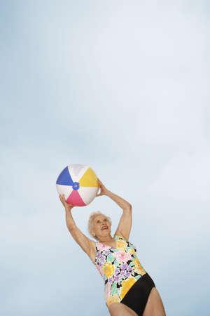bathing costume: Senior woman holding beach ball