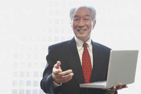 Senior Asian businessman holding laptop Stock Photo - 16094657