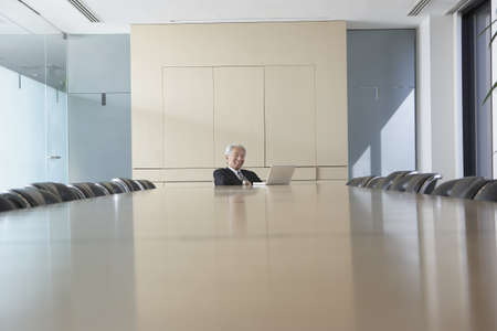 table surface: Senior Asian businessman at conference table